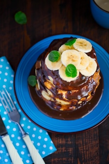 Pile de crêpes à la banane et au chocolat sur une table en bois sombre
