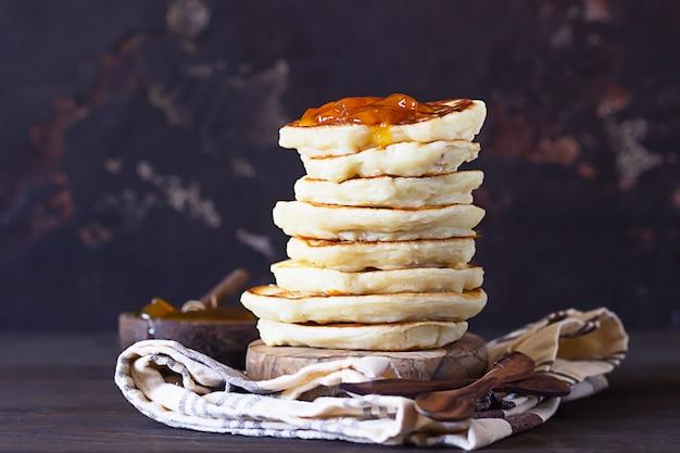 Pile de crêpes ou beignets américains avec une délicieuse confiture d'abricot sur une plaque en bois