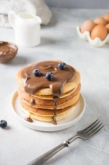 Pile de crêpes maison sucrée au chocolat et aux bleuets sur tableau blanc.
