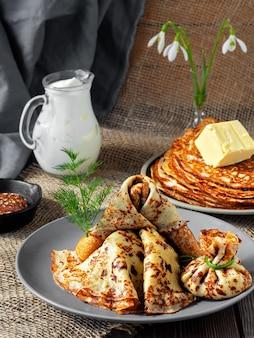 Pile de crêpes russes au beurre et à la crème sure fraîche