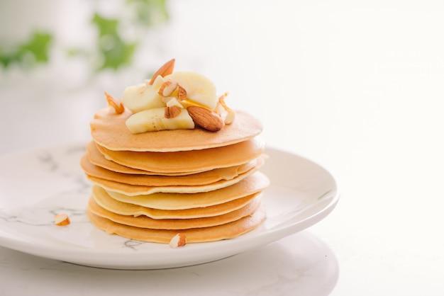 Pile de délicieuses crêpes au chocolat, miel, noix et tranches de banane sur plaque sur fond de pierre