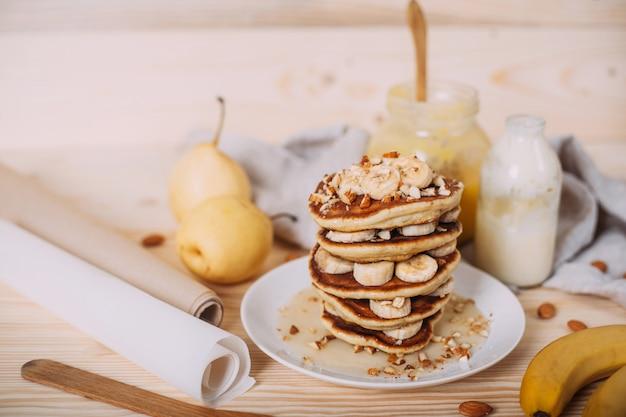 Pile de délicieuses crêpes au miel, aux noix et aux tranches de banane.