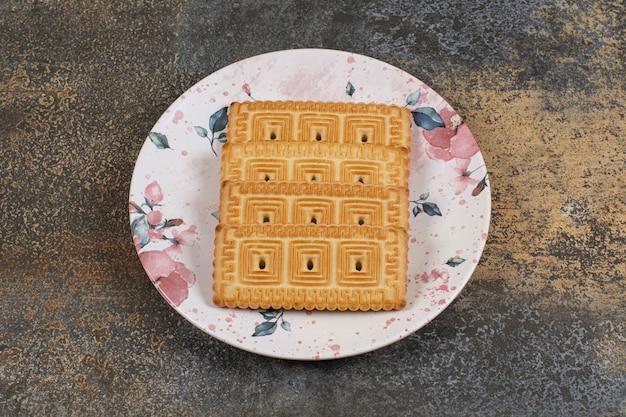 Pile de délicieux biscuits sur assiette colorée.