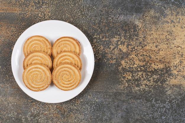 Pile de délicieux biscuits ronds sur plaque blanche.