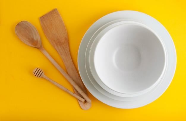 Pile de différentes assiettes blanches, bols. isolé sur fond jaune.