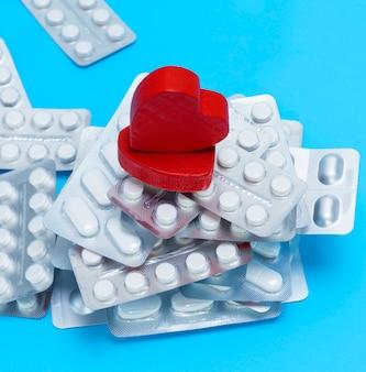 Pile de différentes pilules dans un paquet et deux coeurs rouges