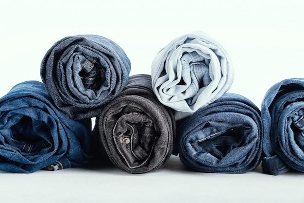 Pile de différents jeans roulés sur blanc