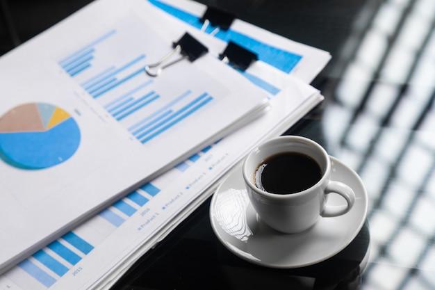 Pile de documents financiers et une tasse de café agrandi