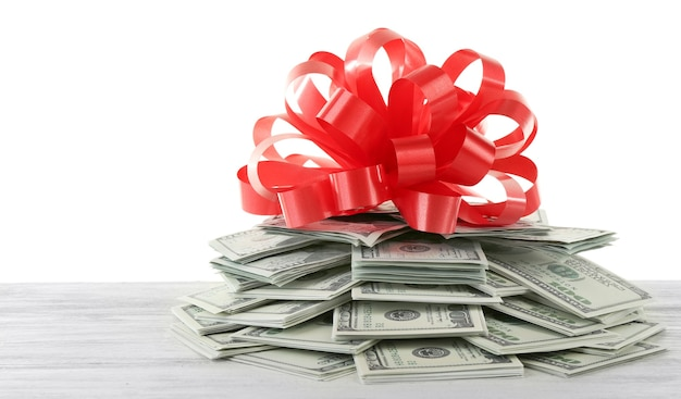 Pile de dollars avec arc en cadeau sur blanc