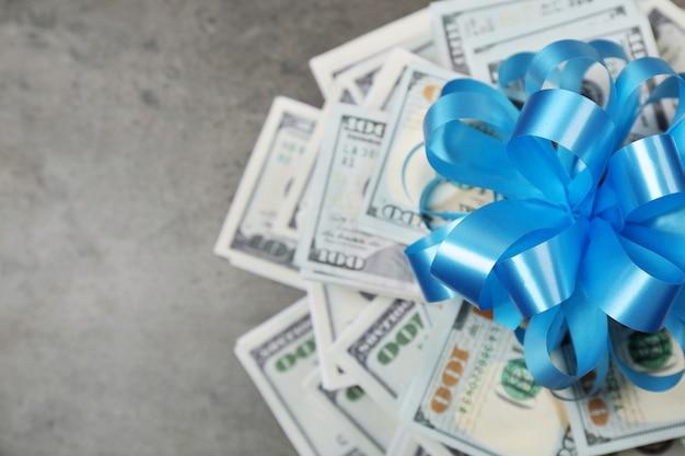 Pile de dollars avec un arc en cadeau sur une table texturée grise