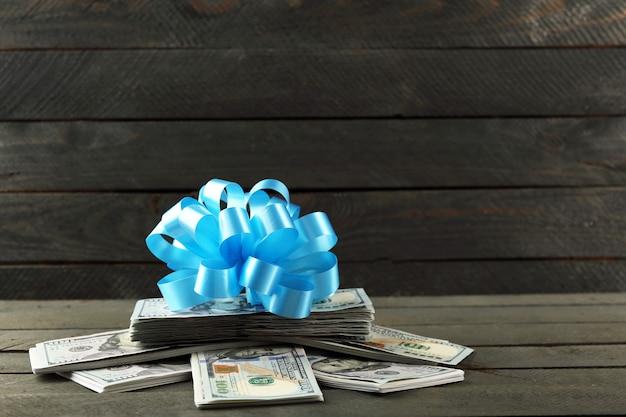 Pile de dollars avec archet comme cadeau sur fond de bois