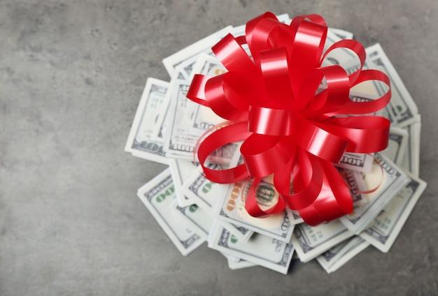Pile de dollars avec archet comme cadeau sur fond texturé gris