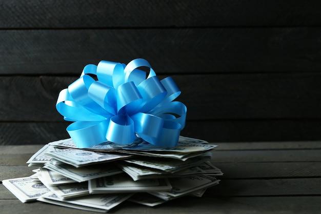 Pile de dollars avec archet comme cadeau sur table en bois