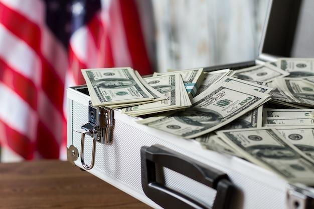 Pile de dollars dans la valise. drapeau des états-unis, argent comptant et étui. plus de chances de victoire. compliment de l'exécutif local.