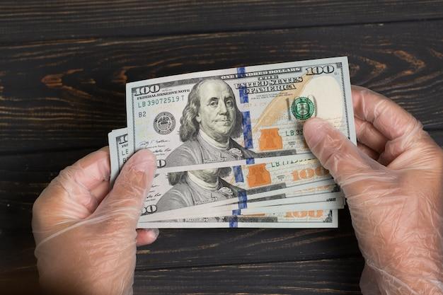 Pile de dollars usa en mains gantées sur table en bois