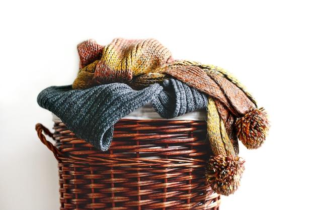 Pile d'écharpes d'hiver tricotées sur panier de paille isolé