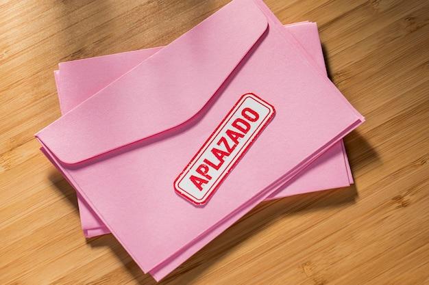 Pile d'enveloppe avec message reporté sur le bureau