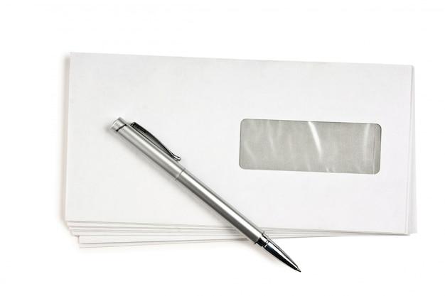 Pile d'enveloppes postales et un stylo isolé
