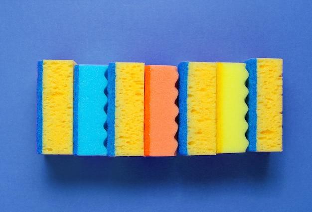 Pile d'éponges de nettoyage colorées isolé sur fond bleu.