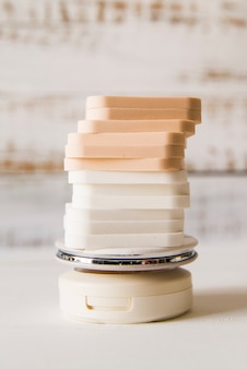 Pile d'éponges sur poudre compacte sur fond blanc