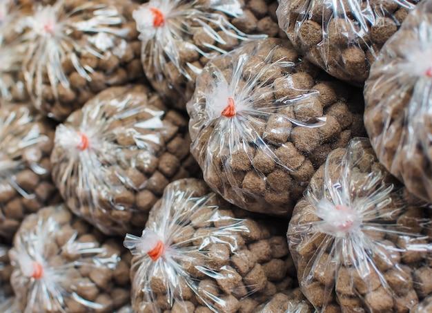 Pile feed pack dans un sac en plastique à vendre au parc public. aliments pour poissons et aliments pour animaux.