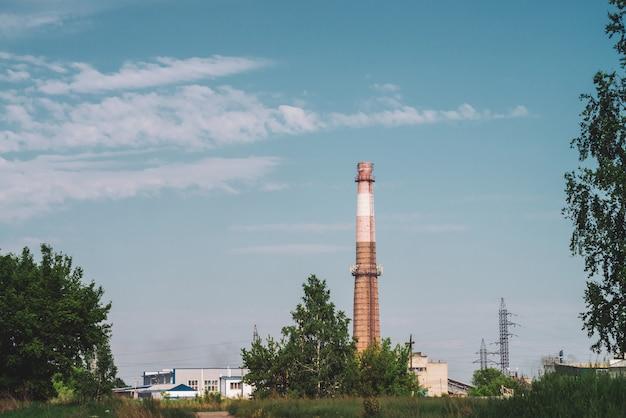 Pile de fumée géante dans la zone industrielle derrière les arbres. structure industrielle avec gros tuyau de brique brune sous ciel bleu. technologie et nature. pollution de l'environnement.