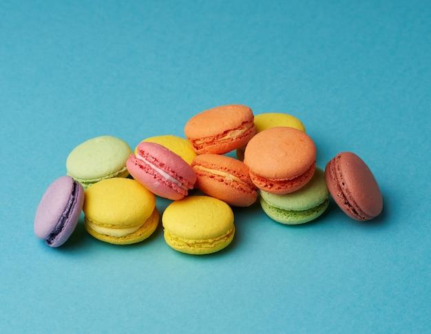 Pile de gâteaux macarons cuits au four rond multicolore sur un bleu