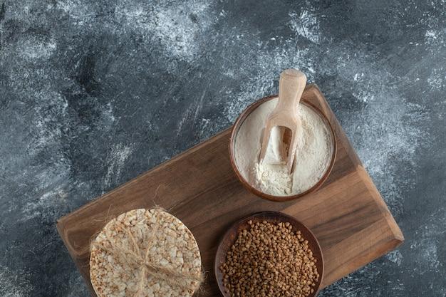 Pile de gâteaux de riz, bol de farine et de sarrasin sur planche de bois