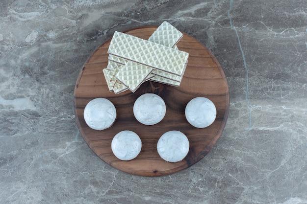 Pile de gaufrettes et biscuits au chocolat blanc sur planche de bois.
