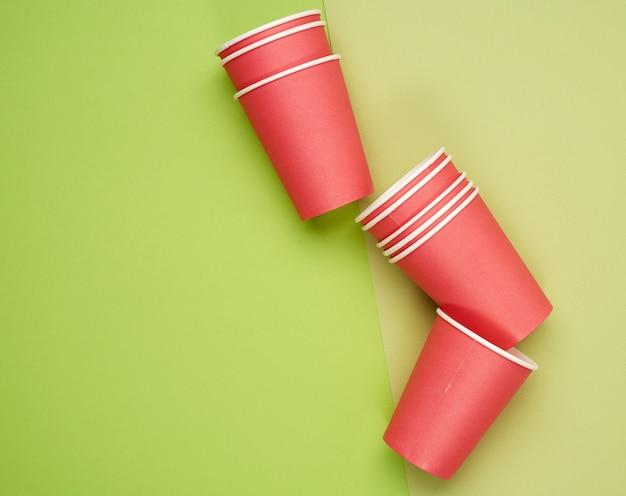 Pile de gobelets jetables en papier rouge sur fond bleu, mise à plat, concept écologique, zéro déchet