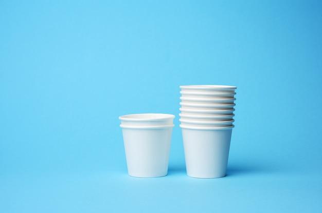 Une pile de gobelets en papier blanc sur fond bleu. concept de rejet de plastique, zéro déchet