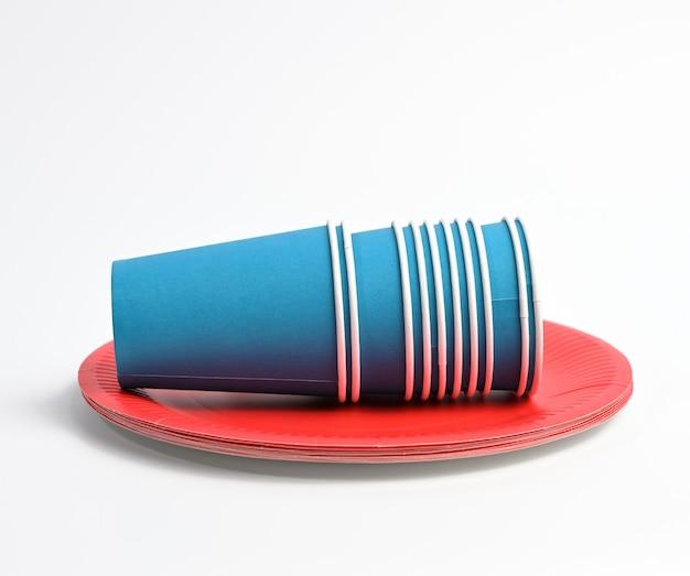 Pile de gobelets en papier bleu et assiettes rondes rouges sur fond blanc. concept de rejet de plastique, zéro déchet