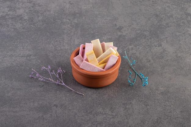Pile de gommes colorées dans un bol de poterie sur fond gris.