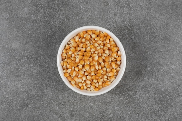 Pile de grains de maïs crus dans un bol blanc.
