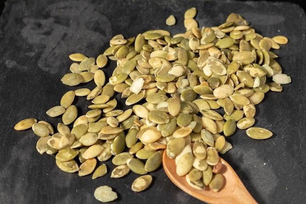 Pile isolée de graines de citrouille décortiquées grillées sur fond noir vu du haut, certaines semblent se déplacer autour de la pile. cuillère en bois avec des graines.