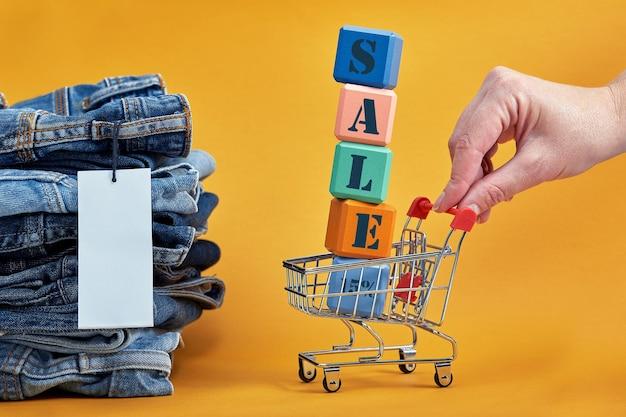 Une pile de jeans bleus avec une étiquette vierge blanche sur fond jaune. chariot de courses avec cubes multicolores. mot de vente écrit sur des cubes. consentement à la vente. tas de pantalons en denim à la mode élégant.