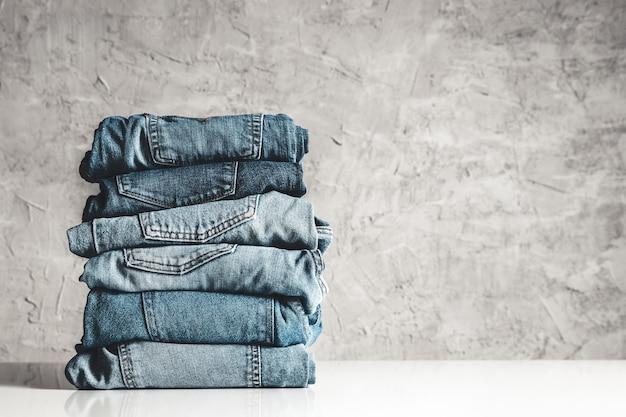 Pile de jeans bleus sur fond gris