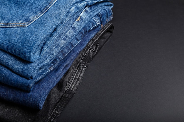 Pile de jeans bleus sur fond noir avec espace de copie. cadre composé d'une pile de pantalons en jean bleu.