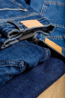 Pile de jeans bleus variés, textiles de jeans denim comme toile de fond. différents pantalons de jeans bleus pilent le fond de tissu de texture textile.