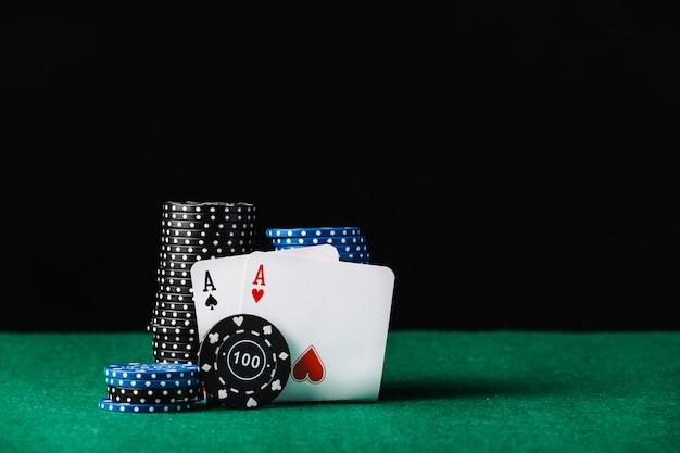 Pile de jetons de casino bleu et noir avec des as de cœur et de pique