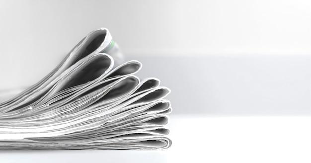 Une pile de journaux frais sur fond gris. nouvelles