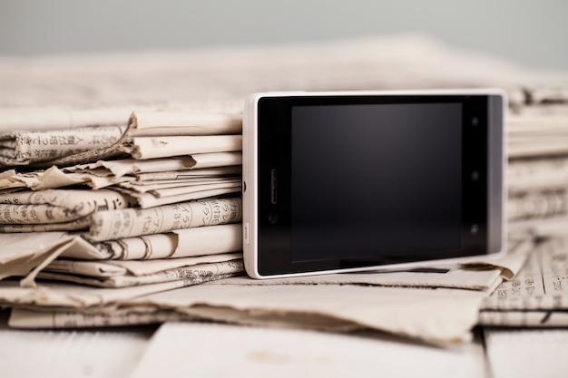 Pile de journaux avec smartphone dessus