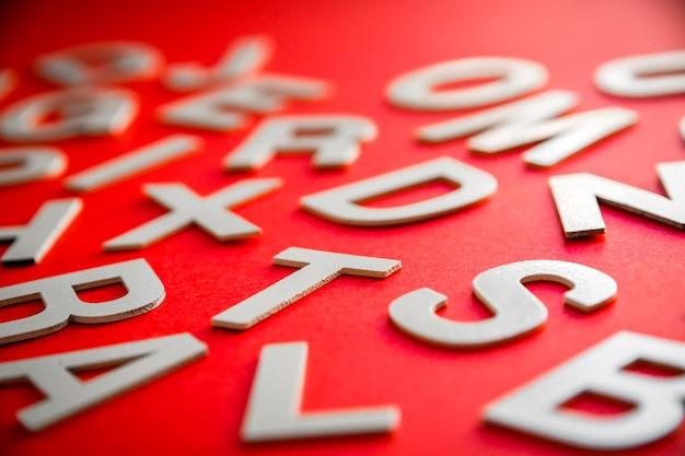 Pile de lettres solides mélangées vue rapprochée photo. concept d'éducation sur fond rouge.
