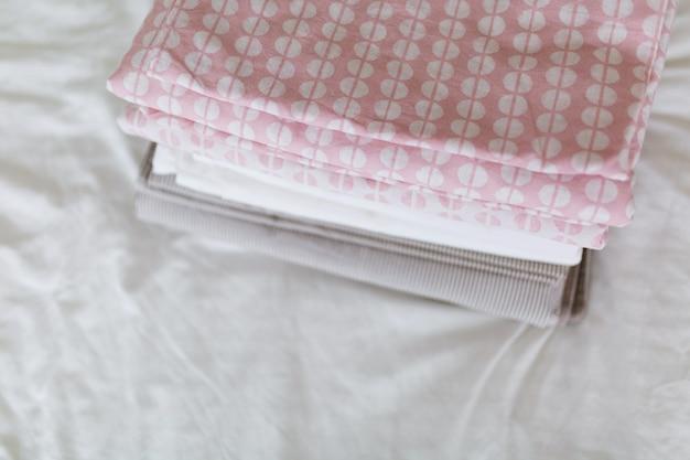 Une pile de linge propre et repassé est sur le lit