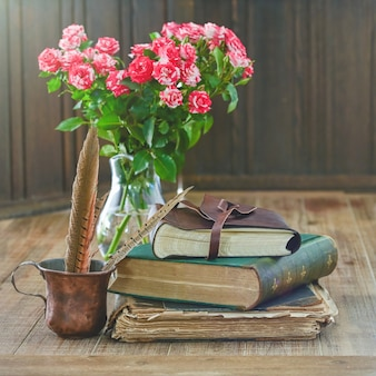 Pile de livres anciens avec bouquet de fleurs roses et une tasse rustique avec des plumes se trouvent sur une table en bois