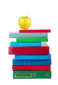 Pile de livres et apple isolé sur une surface blanche