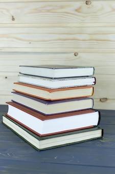 Une pile de livres avec bibliothèque sur le fond d'écran arrière