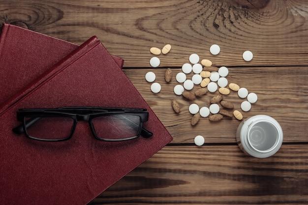 Pile de livres avec bouteille de pilules sur bois. éducation médicale