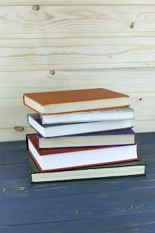Une pile de livres à couverture rigide sur une table en bois. retour à l'école