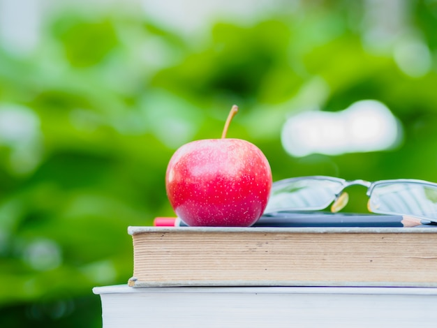 Pile de livres, crayon, lunettes et pomme rouge sur la table en bois